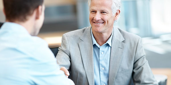 older man in suit shaking hands with man